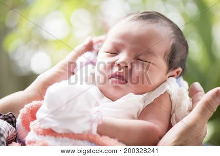 Newborn baby sleeping in mother's hands selective focus in her eyes Family concept
