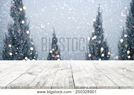 Christmas and New year background with wooden deck table over christmas tree snow and blurred light bokeh. Empty display for product montage. Rustic vintage Xmas background.