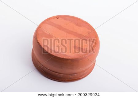 A brown bowl made out of clay up side down on a white surface.