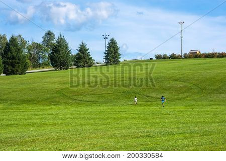 Kids run towards the giant peace sign in the hillside of the Woodstock concert field.