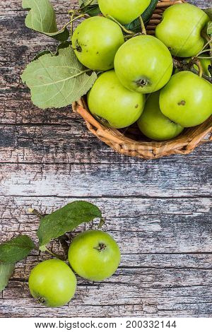 Fresh green apples with leaves in a wicker basket on a old wooden table. A new crop. The concept of a healthy diet. Top view.
