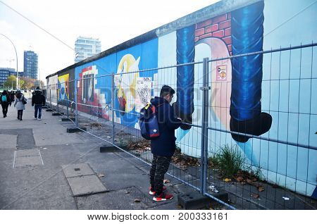 German And Foreigner Travelers Visit And Take Photo With The Berlin Wall (painted On The Eastern And