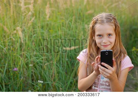 Good girl dials the number on the phone outdoors and going to call her girlfriend. She has 8-9 years