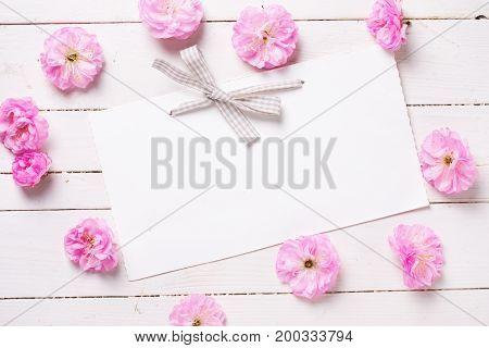 Frame from pink sakura flowers and empty tag on white painted wooden planks. Selective focus. Place for text.