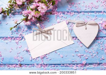 Pink sakura flowers decorative heart and empty tag on blue wooden planks. Selective focus. Place for text. Flat lay. Top view. Shabby chic.