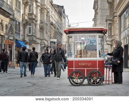 Istanbul Turkey - April 24 2017: Old Turkish lady buying fast food meal from a traditional Turkish Simit (Turkish Bagel) cart in Istiklal street and people walking at afternoon