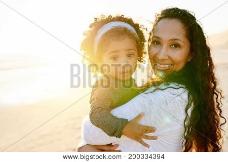 Smiling African-American woman holding her daughter and looking at camera on shore in evening.
