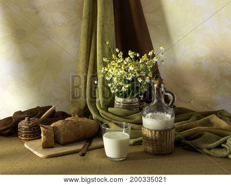 Still life with daisies, bread and milk on the table close-up
