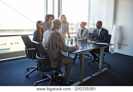 Work Colleagues Discussing Business Together In An Office Boardroom