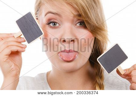 School education learning concept. Teenage girl holding little school blackboards and ticking her tongue out. Studio shot on white background.