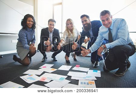 Positive Businesspeople Giving The Thumbs Up In An Office