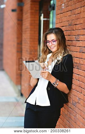 Business Girl in a jacket and glasses with a tablet near a brick wall on the street