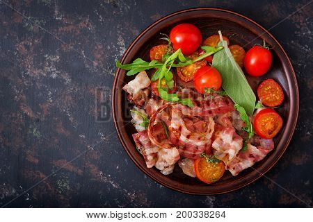Fried Bacon And Tomatoes In Plate On A Dark Background. Flat Lay. Top View.