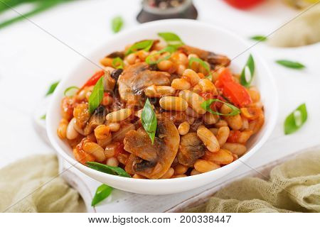 Stewed White Beans With Mushrooms And Tomatoes With Spicy Sauce In A White Bowl.