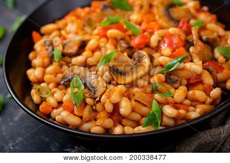 Stewed White Beans With Mushrooms And Tomatoes With Spicy Sauce In A Black Bowl.