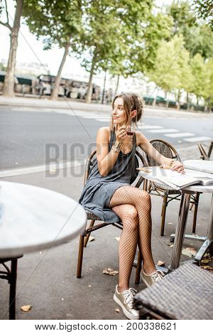 Young stylish woman in gray dress and cabaret tights sitting outdoors at the cafe in Paris poster