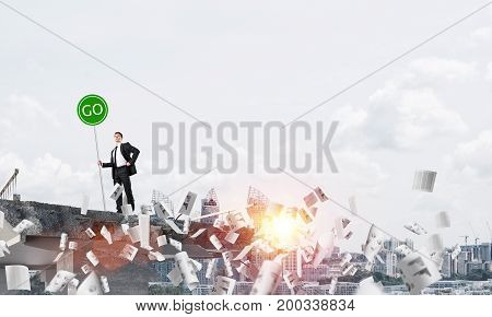 Confident businessman in suit holding green go sign while standing among flying papers on broken bridge with cityscape and sunlight on background. 3D rendering.