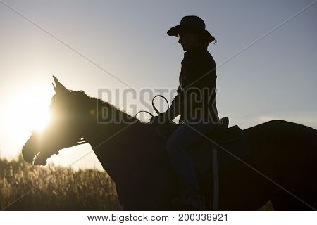 Silhouette of a woman riding a horse - sunset or sunrise, horizontal, telephoto