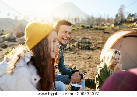 Group of laughing friends sitting and talking together while drinking cups of coffee at their campsite in the early morning