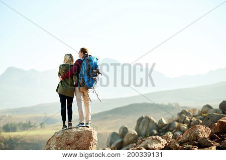 Young Couple Admiring The Mountain View While Hiking Together