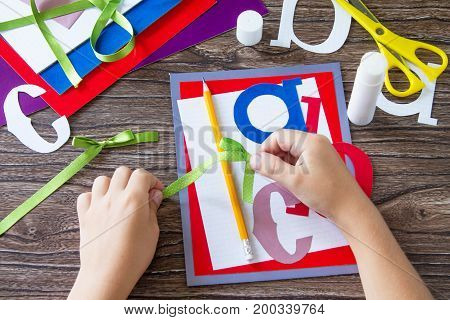 The Child Ties The Tape Of The Ribbon Details Of The Applique. Greeting Card With A Pencil And Lette