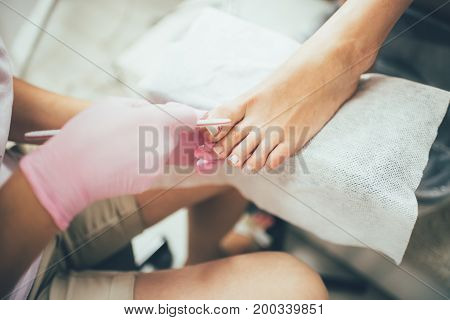 Female hands making a pedicure. Beauty salon, female feet, real picture of nail care.