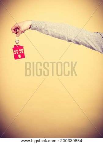 Closeup male hand holding new house key with red home shape. Real estate and housing concept.