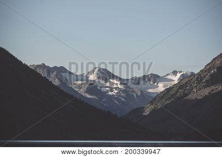Gloomy landscape with lake and Snow caps the high mountains in the background in evening light. Dark the severe nature of Siberia the Altai. a calm sea with mountains in the background