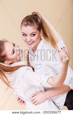 Fun bonding selfie concept. Sisters or best friends two student blonde girls taking self photo with smart phone camera having fun positive funny emotion on face