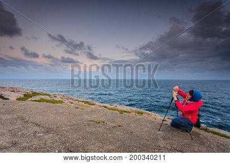 Woman photographer taking photo with camera on the most southern point of Norway in Lindesnes South Cape Vest-Agder Norway