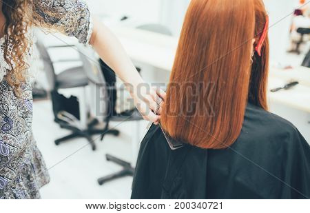 Stylist working in the beauty salon, haircut and hair styling. Modern hair care.