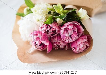 Bouquet of pink tulip flowers on table in brown paper close-up
