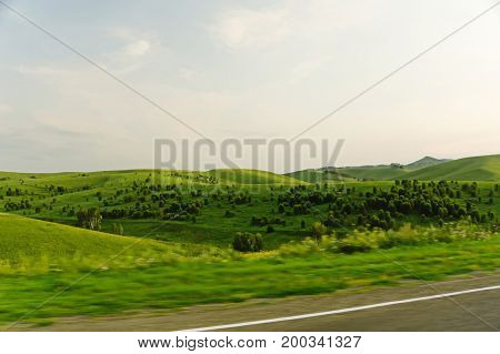 The Road Overlooking A Beautiful Field With Trees On The Slopes.