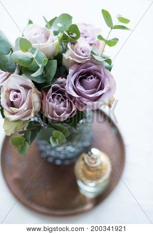 Pastel purple, mauve color fresh summer roses in vase in tray closeup, vintage style