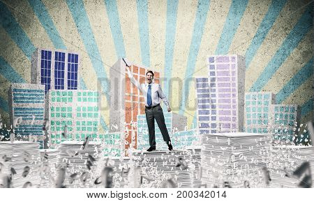 Businessman keeping hand with book up while standing among flying letters with drawn cityscape on background. Mixed media.