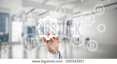 Close of businesswoman hand touching gears on screen with finger and office at background