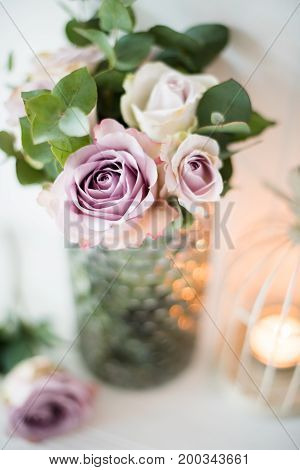Pastel purple, mauve color fresh summer roses in vase with white wall background and candles, vintage style wedding decor