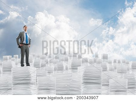 Confident businessman in suit standing on pile of documents and looking away with cloudly skyscape on background. Mixed media.