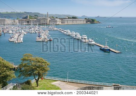 PLYMOUTH UK. August 19th 2017. Plymouth's Royal William Yard and Breakwater viewed from the hilltop of Mount Wise green trees in the foreground. The Willaim Yard has become a major draw for tourists to the city of Plymouth over the last few years.