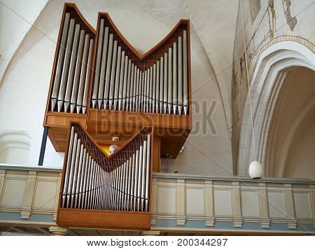 Big classical traditional metal pipe organ in a church religion heritage