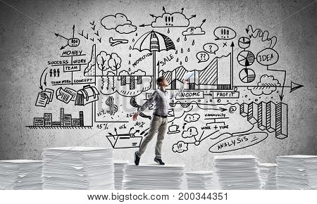 Man in casual wear keeping hand with book up while standing against business-plan information on background. Mixed media.