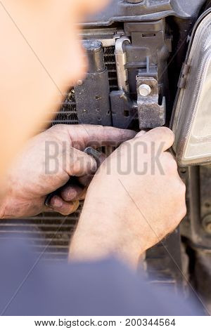 Manual worker dismantling a car to pieces to fix the problem.
