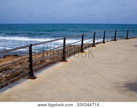 Beautiful beach seaside promenade with metal railings summer vacation attraction Spain