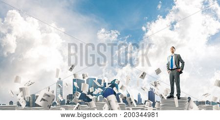 Confident businessman in suit standing on pile of documents among flying papers with cloudly sky on background. Mixed media.