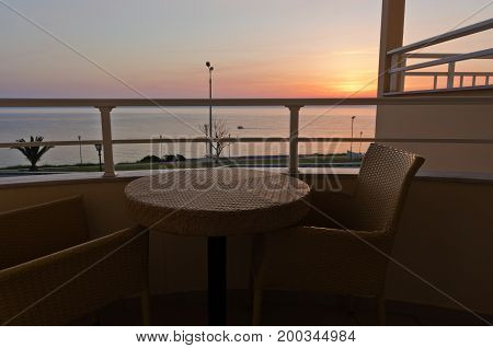 Table and two chairs on a balcony by the sea at sunrise in Greece