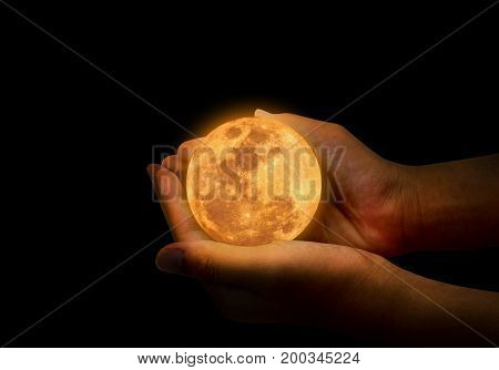 Female hand hold yellow full moon on her hand. A full moon is the lunar phase that occurs when the Moon is completely illuminated as seen from Earth.