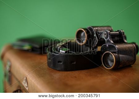 Old binoculars and belt on suitcase. Travel concept.