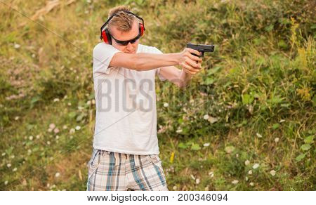 Young And Strong Caucasian Blond Guy Firing Bullets At The Enemy Target In The Wilderness. Aiming To