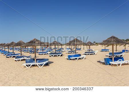 Summer morning on the Algarve beach. Sunbeds on the sand.