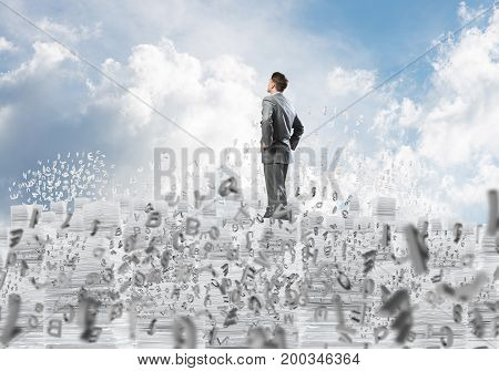 Confident businessman in suit standing on pile of documents among flying letters with cloudly skyscape on background. Mixed media.
